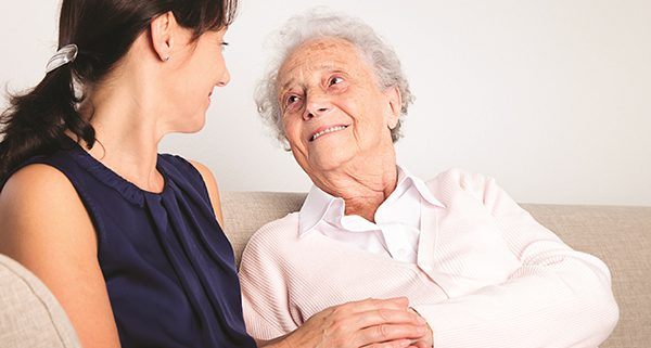 senior woman holding hand with younger woman