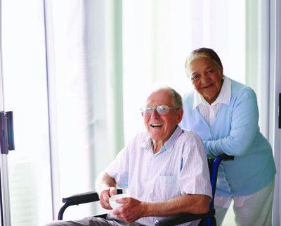 senior woman with senior man on wheelchair