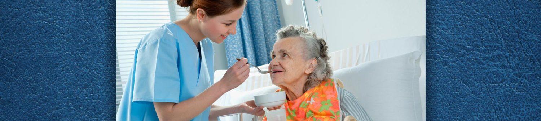 caregiver feeding soup to senior woman