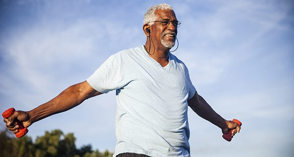 Senior Man Exercising Outdoors with Dumbells