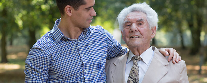 young marn with arm around senior man, Alzheimer's