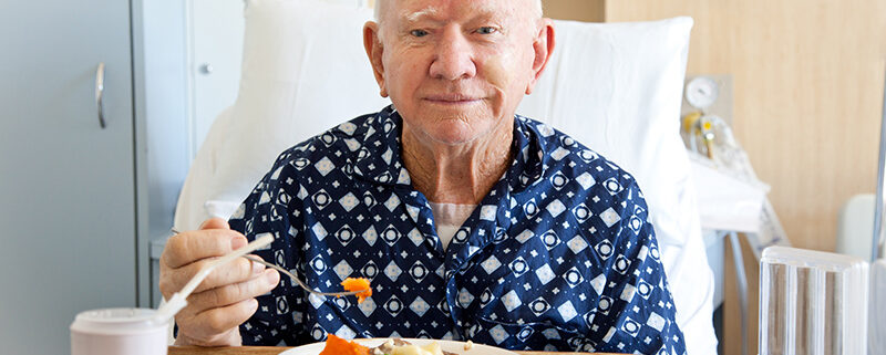 Senior male patient in hospital eating lunch
