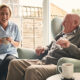 Senior man and female carer enjoying coffee at home