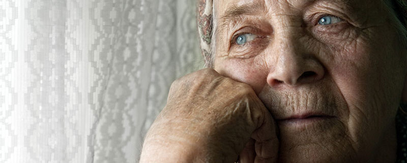 sad senior woman looking out
